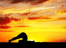 Yoga silhouette Halasana plough pose Royalty Free Stock Photo