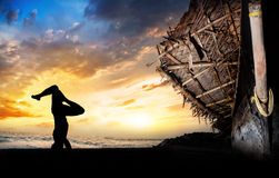 Yoga silhouette head stand. Man silhouette doing shirshasana head stand pose on the beach near the fisherman boat at sunset background in Varkala, Kerala, India Royalty Free Stock Image