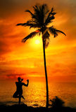 Yoga silhouette lord krishna pose. Yoga lord krishna pose by Man in silhouette with palm tree nearby outdoors at ocean and sunset background. Vagator beach, Goa Stock Photography