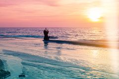Yoga silhouette. Meditation fitness woman on the ocean during amazing sunset. Healthy lifestyle. stock photography