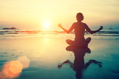 Yoga silhouette. Meditation girl on the sea during sunset. Royalty Free Stock Photography