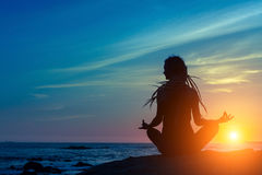 Yoga silhouette. Meditation woman on the ocean during amazing sunset. Fitness and healthy lifestyle Stock Images