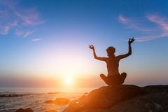Yoga silhouette meditation woman on the ocean during amazing sunset. Healthy lifestyle Royalty Free Stock Photography