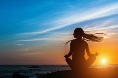 Yoga silhouette meditation woman on the ocean during sunset. Yoga silhouette meditation woman on the ocean during amazing sunset Stock Photos