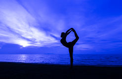Yoga. Silhouette one woman with professional yoga posture on the beach at sunset Royalty Free Stock Images