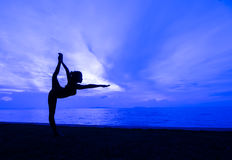Yoga. Silhouette one woman with professional yoga posture on the beach at sunset Stock Photos