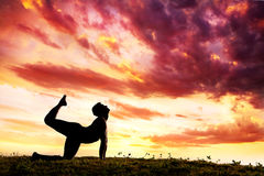 Yoga silhouette parshva marjariasana cat pose. Parshva marjariasana cat pose by Man silhouette outdoors at sunset background. Free space for text Royalty Free Stock Photo