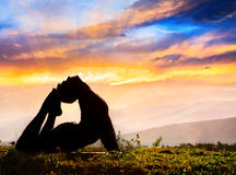 Yoga silhouette Raja Kapotasana pose. Yoga Raja Kapotasana backward bending pose by Man in silhouette on the grass outdoors at mountains and cloudy sky with Royalty Free Stock Photography