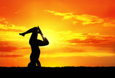 Yoga silhouette shirshasana pose. Yoga shirshasana head standing inverse pose with bending legs by Man in silhouette with orange sunset sky background. Free Royalty Free Stock Image