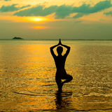 Yoga silhouette at sunset. Yoga women silhouette, working on poses at sunset Stock Image