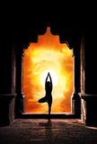 Yoga silhouette in temple. Yoga vrikshasana tree pose by man silhouette in old temple arch at dramatic sunset sky background. Free space for text Royalty Free Stock Images