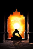 Yoga silhouette in temple. Yoga raja kapotasana pigeon pose by man silhouette in old temple at dramatic sunset sky background. Free space for text Stock Photos