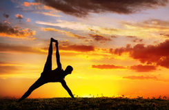 Yoga silhouette Vasisthasana plank pose. Yoga Vasisthasana plank balancing pose by Man in silhouette with dramatic sunset sky background. Free space for text Royalty Free Stock Photo
