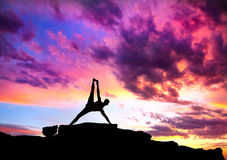 Yoga silhouette Vasisthasana plank pose. Yoga Vasisthasana plank balancing pose by Man in silhouette on the rock outdoors at mountains and cloudy sky background Stock Photo