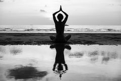 Yoga silhouette. Woman doing meditation near the ocean beach. Black and white photo Royalty Free Stock Image