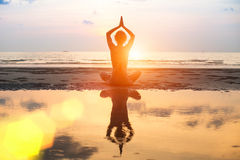 Yoga, silhouette young woman on the beach at sunset. Stock Image