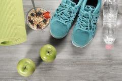 Yoga som är matt med sportskor och sund mat Royaltyfri Bild