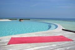 Yoga som är matt vid simbassängen bredvid havet Arkivbild