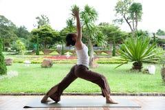 Yoga som poserar i trädgård Royaltyfri Bild