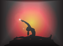 Yoga Splits Pose Glare Background. A yoga woman silhouette performing splits pose on a dark colourful background with a glare Stock Images