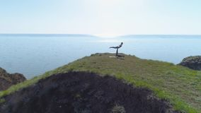 Yoga sport, yogi athletes family perform paired balancing exercises Outdoors on cliff near sea against sunny sky. Aerial view stock video