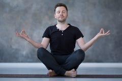 Yoga stelt de mannelijke beginner het praktizeren yogazitting binnen en mediteert royalty-vrije stock foto's