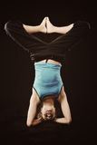 Yoga stick figure. Young woman in tracksuit do yoga poses on head royalty free stock image