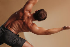 Yoga Stretch. Male back in gray shorts finding zen through yoga Stock Photography
