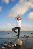 Yoga Stretch. Beautiful woman doing yoga exercises on the beach Stock Image