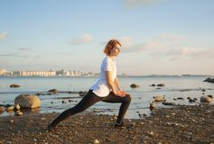 Yoga Stretch. Beautiful woman doing yoga exercises on the beach Stock Photo