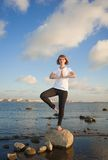 Yoga Stretch. Beautiful woman doing yoga exercises on the beach Stock Images