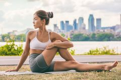 Free Yoga Stretch Exercise Fit Asian Woman Stretching Lower Back For Spine Health On City Outdoor Fitness Class In Park. Seated Spinal Stock Photo - 154999670