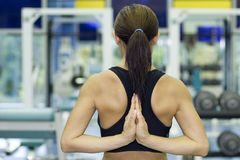Yoga Stretch In Gym. A female fitness instructor stretches her arms in a yoga pose in a gym Royalty Free Stock Images