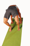 Yoga stretch Isolated. Male back in gray shorts finding zen through yoga in a strange arching position on a green matt Royalty Free Stock Photo