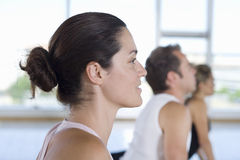 Yoga students in cobra position in class in studio, side view, close-up Stock Images