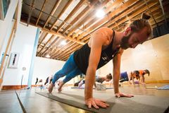 Yoga Studio Editorial. SPRINGFIELD, OR - MARCH 11, 2018: Advanced yogi and male yoga instructor Ben Wilkinson working out during a teaching class at Common Bond Stock Image