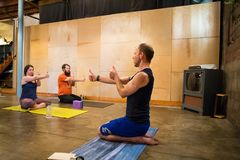 Yoga Studio Editorial. SPRINGFIELD, OR - MARCH 11, 2018: Male yoga instructor teaching an intermediate class at Common Bond Yoga, an urban yoga startup company Royalty Free Stock Image