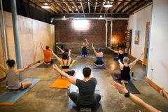Yoga Studio Editorial. SPRINGFIELD, OR - MARCH 11, 2018: Male yoga instructor teaching an intermediate class at Common Bond Yoga, an urban yoga startup company Stock Images