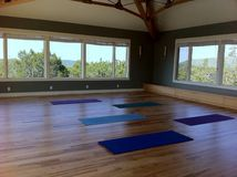 Yoga mats in a studio classroom with wood floors. Mats in an empty yoga studio with wood floors and natural light at a resort in Texas Stock Photos