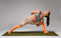 Yoga in studio. Woman. Beautiful yogi doing yoga in parivrtta parshvakonasana pose. Studio Royalty Free Stock Images