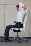 Yoga sulla sedia in ufficio - esercitazione dell'uomo di affari Fotografie Stock