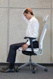 Yoga sulla sedia in ufficio - esercitazione dell'uomo di affari Fotografia Stock