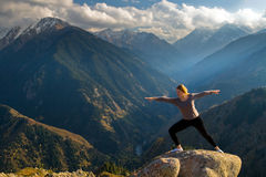 Yoga at summit. With aerial view of the mountain range and peak, with sunlight Royalty Free Stock Photography