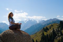 Yoga at summit. With aerial view of the mountain range Royalty Free Stock Images