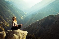 Yoga at summit. With aerial view of the mountain range and peak. Blue sky Stock Photography