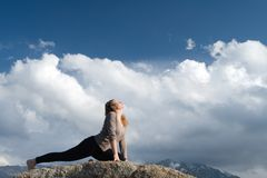 Yoga at summit. With aerial view of the mountain range and peak. Blue sky Royalty Free Stock Photo