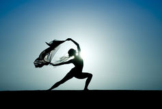 Yoga at Sunrise. Silhouette of a woman in a yoga pose, backlit by the sun Stock Photography