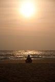 Yoga on sunset. Silhouette of man making yoga in meditation pose on sunset beach Stock Image