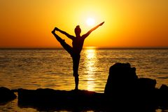 Yoga on sunset. Woman making yoga figure on the beach at sunset Stock Photography