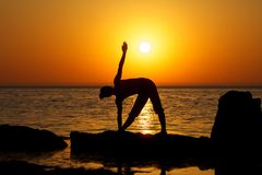 Yoga on sunset. Woman making yoga figure on the beach at sunset Royalty Free Stock Images